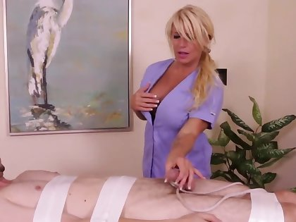 Tanned blonde masseuse with big breasts focuses on a handjob